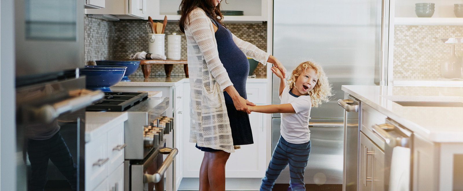 A mother and child happily dancing in a kitchen