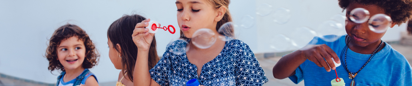children outside blowing bubbles