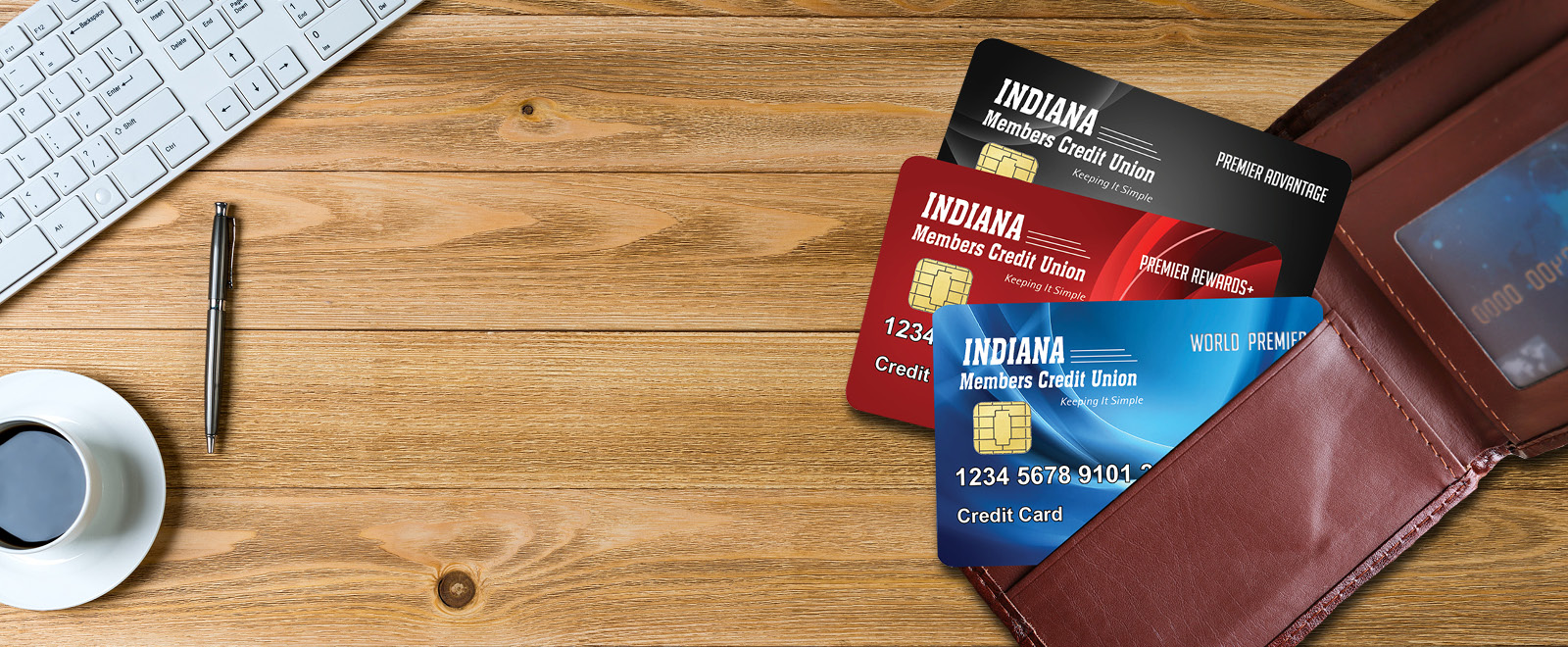 Indiana Members Credit Union credit cards World Premier, Premier Rewards+ and Premier Advantage on top of a wood table.